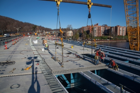 Crews place road deck panels on top of the blue girders we can see while driving/NYSTA
